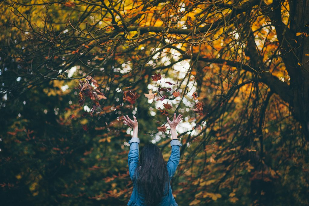 Woman throwing fall leaves